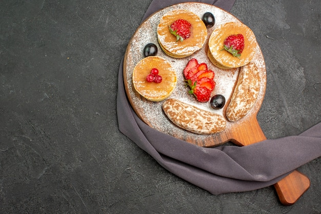 Vista de cima deliciosas panquecas com frutas e bolos doces no escuro
