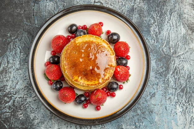 Vista de cima deliciosas panquecas com frutas e mel na luz