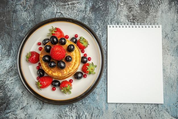 Vista de cima deliciosas panquecas com frutas e morangos em bolo de frutas de sobremesa de superfície clara