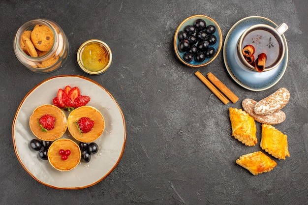 Vista de cima deliciosas panquecas com frutas e uma xícara de chá no escuro