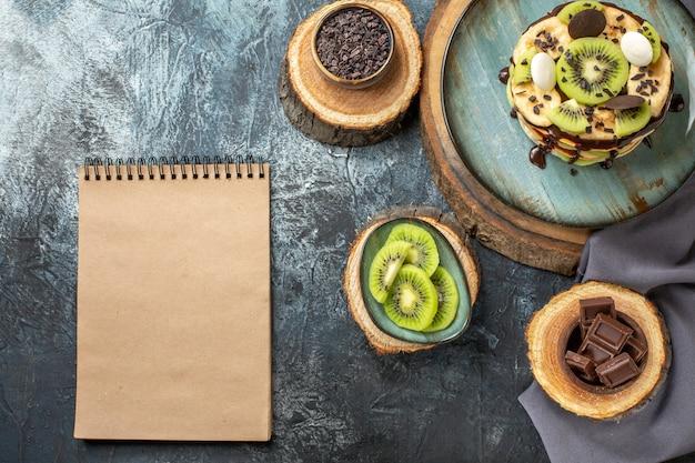 Vista de cima deliciosas panquecas com frutas fatiadas e chocolate na superfície cinza-escuro bolo cor doce café da manhã açúcar frutas sobremesa