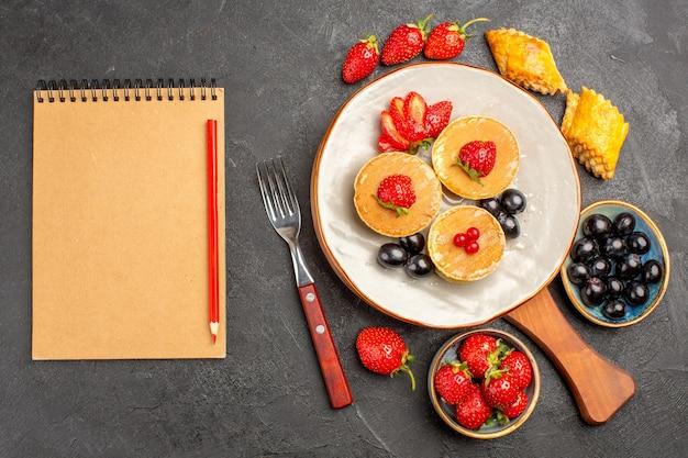Vista de cima deliciosas panquecas com frutas na superfície escura torta bolo de frutas doce