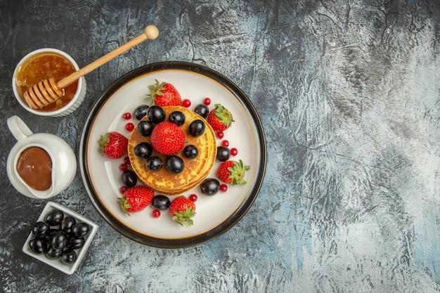 Vista de cima deliciosas panquecas com mel e frutas em um bolo de frutas de superfície clara
