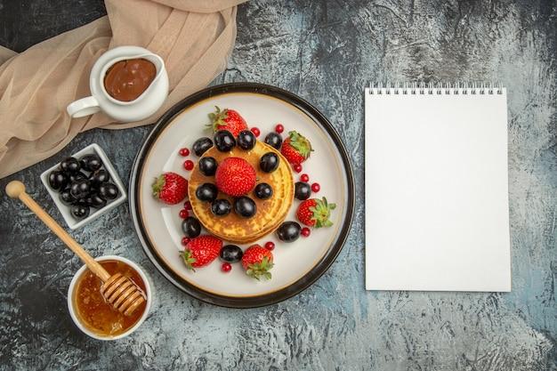 Vista de cima deliciosas panquecas com mel e frutas em uma superfície clara de bolo doce de frutas