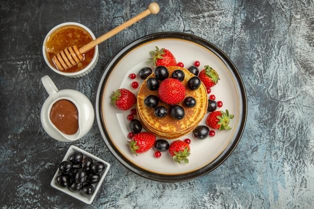 Vista de cima deliciosas panquecas com mel e frutas no bolo de superfície leve frutas doces