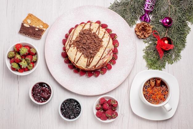 Vista de cima deliciosas panquecas com morangos e xícara de chá na mesa branca torta bolo fruta biscoito doce baga