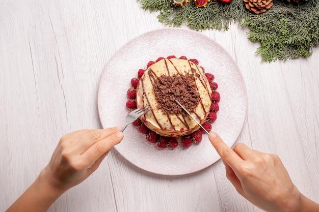 Vista de cima deliciosas panquecas com morangos em uma torta de mesa branca clara, biscoito de frutas e bolo doce de frutas vermelhas