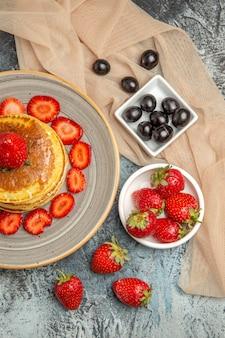 Vista de cima deliciosas panquecas com morangos frescos em uma superfície clara de bolo doce de frutas