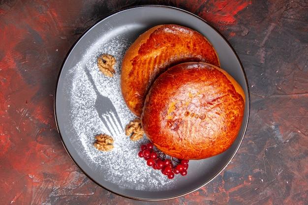 Vista de cima deliciosas tortas com frutas vermelhas em uma mesa escura