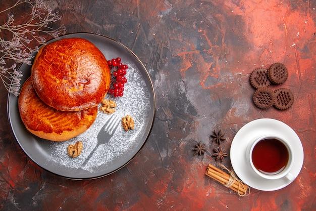 Vista de cima deliciosas tortas com uma xícara de chá em piso escuro torta de bolo doce