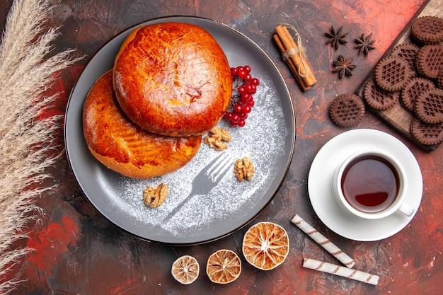 Vista de cima deliciosas tortas com uma xícara de chá na mesa escura de bolo de torta doce