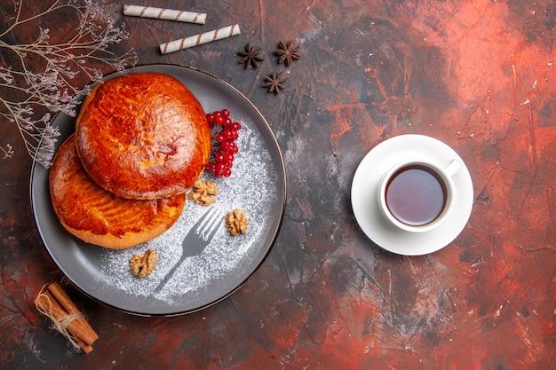 Vista de cima deliciosas tortas com uma xícara de chá na mesa escura torta de bolo doce