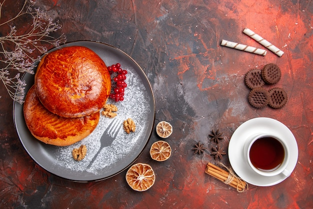 Vista de cima deliciosas tortas com uma xícara de chá na mesa escura tortas de bolo doce
