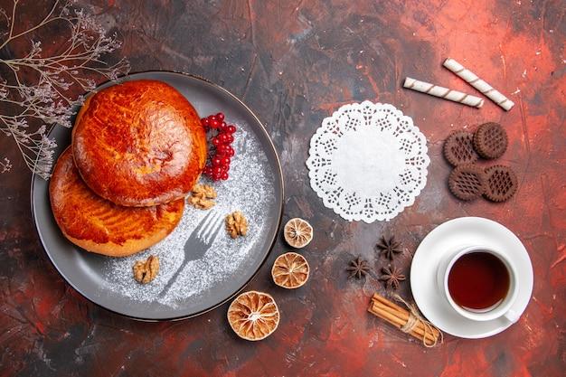 Vista de cima deliciosas tortas com uma xícara de chá na mesa escura