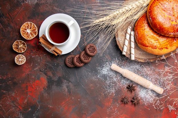 Vista de cima deliciosas tortas com uma xícara de chá na torta de confeitaria de piso escuro