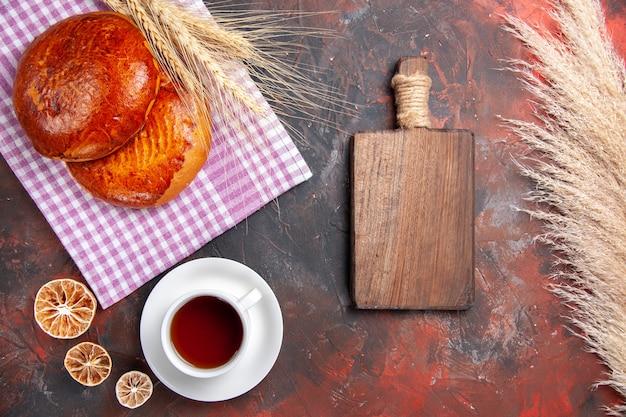 Vista de cima deliciosas tortas doces com uma xícara de chá na mesa escura torta de bolo doce