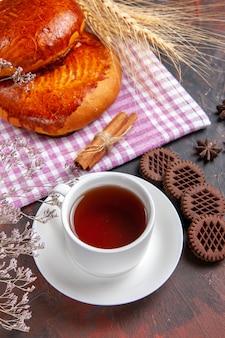 Vista de cima deliciosas tortas doces com xícara de chá na mesa escura