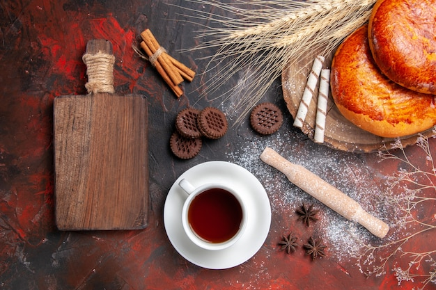 Vista de cima deliciosas tortas para uma xícara de chá na mesa escura