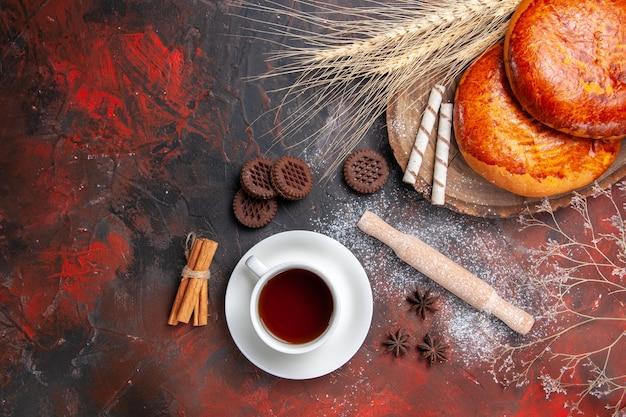 Vista de cima deliciosas tortas para uma xícara de chá na torta de bolo doce de mesa escura
