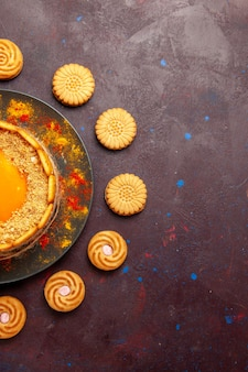 Vista de cima, delicioso bolo amarelo, sobremesa cremosa com biscoitos na mesa escura