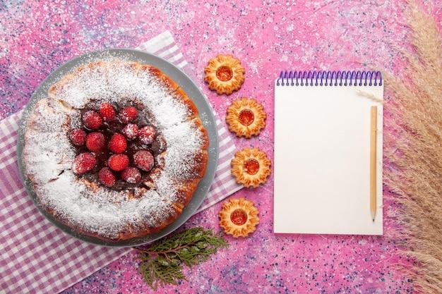 Vista de cima delicioso bolo de morango com bloco de notas e superfície rosa claro