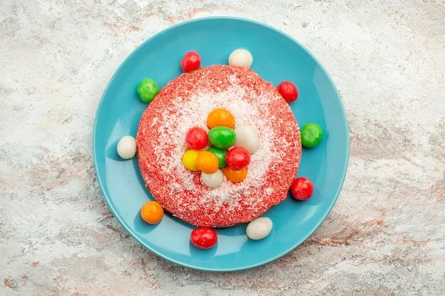 Vista de cima - delicioso bolo rosa com doces coloridos dentro do prato na superfície branca.
