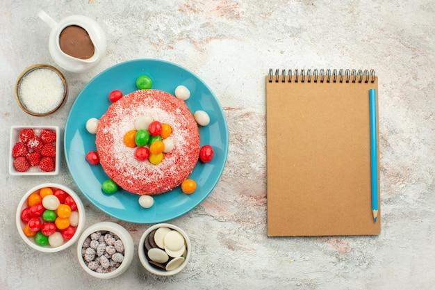Vista de cima - delicioso bolo rosa com doces coloridos e biscoitos na superfície branca.
