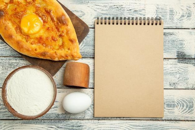 Vista de cima, delicioso pão com ovo cozido com farinha e bloco de notas em uma mesa rústica