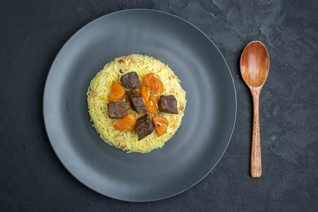 Vista de cima, delicioso pilaf cozido de arroz com damascos secos e fatias de carne dentro do prato em superfície escura
