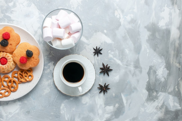 Vista de cima deliciosos bagels com biscoitos e bolos com chá na mesa branca clara.