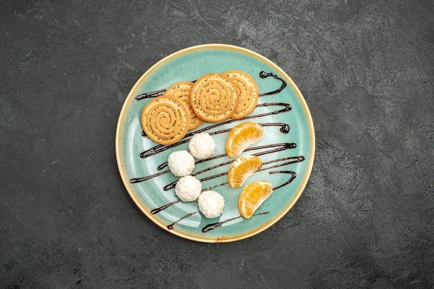 Vista de cima deliciosos biscoitos com bombons de coco e frutas na mesa cinza Foto gratuita