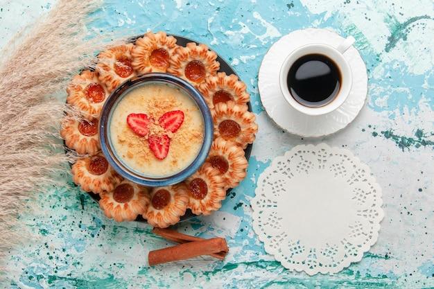 Vista de cima deliciosos biscoitos com geléia de café e sobremesa de morango na superfície azul