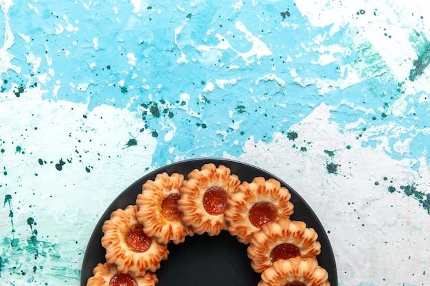 Vista de cima deliciosos biscoitos redondos formados com geleia dentro da placa preta sobre fundo azul claro.
