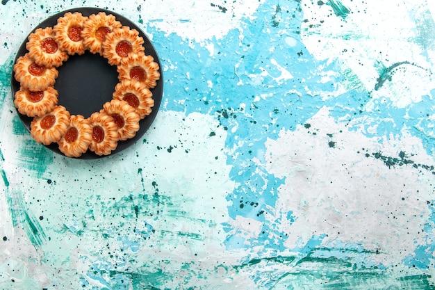 Vista de cima deliciosos biscoitos redondos formados com geleia dentro de uma placa preta no fundo azul claro.