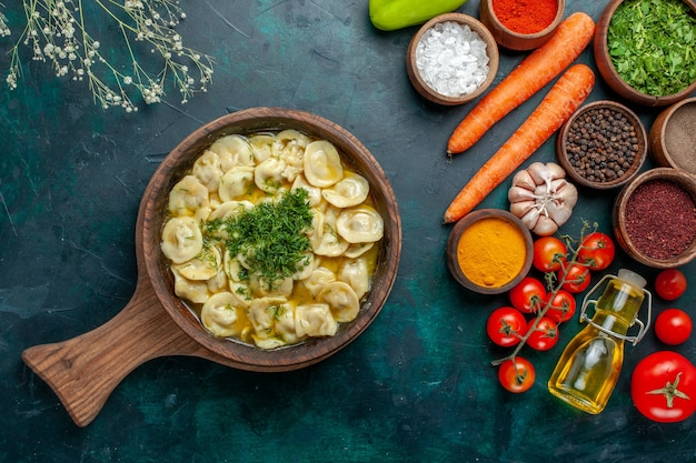 Vista de cima deliciosos bolinhos de massa com vegetais e diferentes temperos na superfície verde-escura refeição ingrediente alimentar produto massa carne