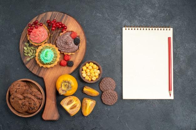 Vista de cima deliciosos bolos com biscoitos e frutas em um bolo de torta doce de mesa escura