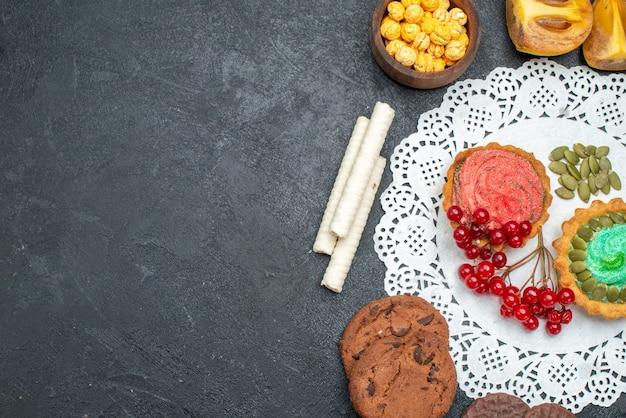 Vista de cima deliciosos bolos com biscoitos e frutas na mesa escura torta de sobremesa doce