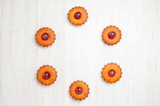 Vista de cima deliciosos bolos com uvas na mesa branca, biscoitos e biscoitos para sobremesa