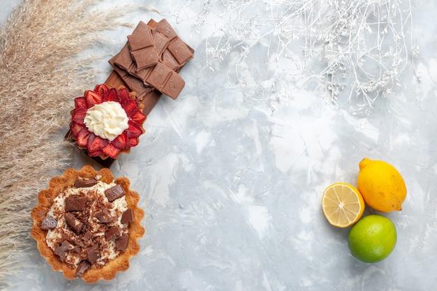 Vista de cima deliciosos bolos cremosos com barras de chocolate e limões frescos na mesa branca bolo biscoito doce assar açucar