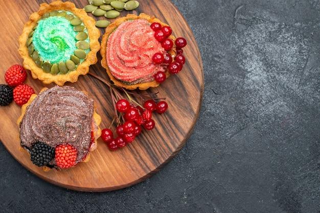 Vista de cima deliciosos bolos cremosos com frutas em doces de biscoito de mesa escura