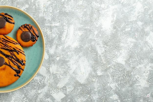 Vista de cima deliciosos bolos de cacau com cobertura de chocolate dentro do prato em uma torta de biscoito doce com piso branco