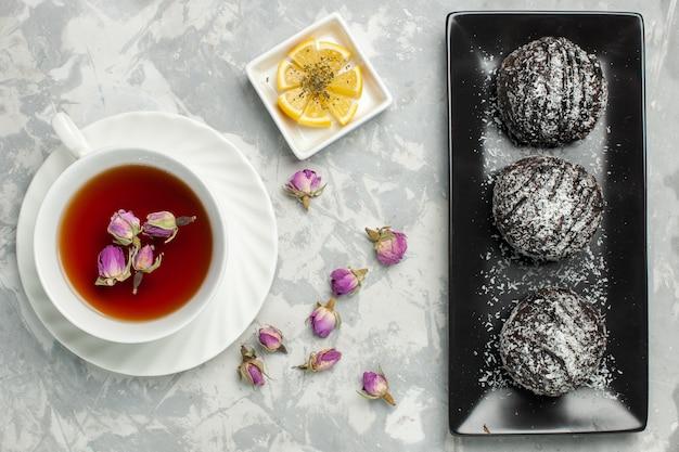 Vista de cima deliciosos bolos de chocolate com cobertura junto com uma xícara de chá em um bolo de mesa branco-claro biscoito açúcar biscoito doce chocolate cacau