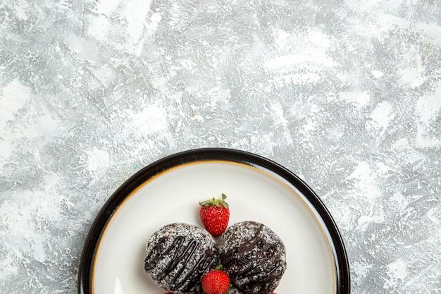 Vista de cima deliciosos bolos de chocolate com morangos vermelhos frescos na mesa branca