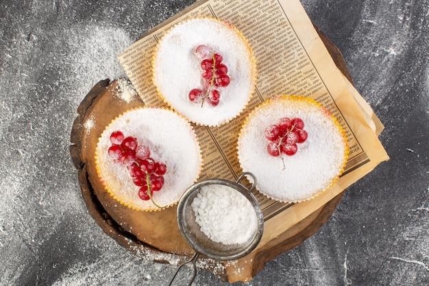 Vista de cima deliciosos bolos de cranberry com cranberries vermelhos em pedaços de açúcar e biscoito de mesa cinza em pó.