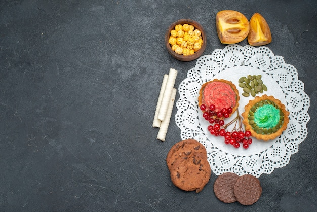 Vista de cima deliciosos bolos de creme com biscoitos e frutas na mesa escura torta de sobremesa doce