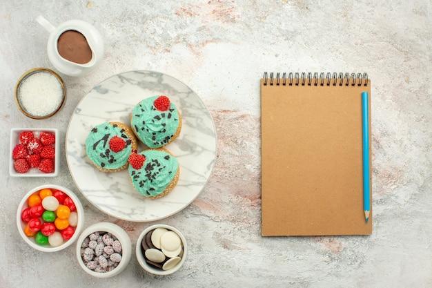 Vista de cima deliciosos bolos de creme com doces coloridos e biscoitos no fundo branco.