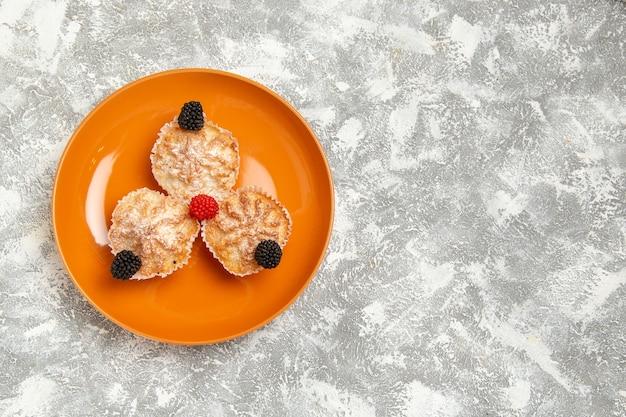 Vista de cima deliciosos bolos de massa com açúcar em pó dentro do prato na mesa branca