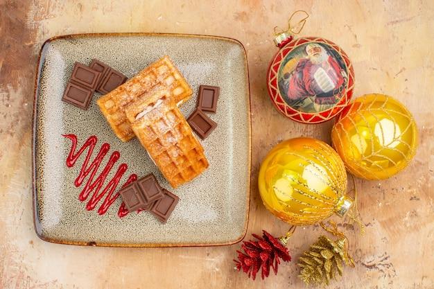 Vista de cima deliciosos bolos de waffle com chocolate e brinquedos de árvore de ano novo no fundo claro