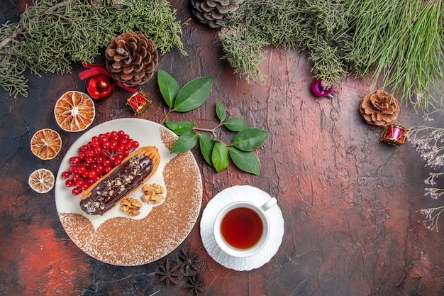 Vista de cima deliciosos choco eclairs com chá e frutas vermelhas na mesa escura, bolo doce, torta, sobremesa