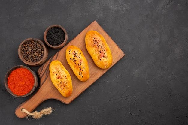 Vista de cima deliciosos hambúrgueres recém-saídos do forno com temperos em fundo cinza torta pastelaria de forno bolo de carne assar